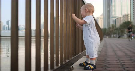 korkuluk : Laughing boy at the age of 1 year dancing holding the railing and learning to walk making the first steps standing in a white jumpsuit on the waterfront Stok Video