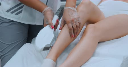 발목 : Laser hair removal procedure in beauty clinic, close up woman legs during epilation, slow motion. Concept of women beauty, cosmetology.