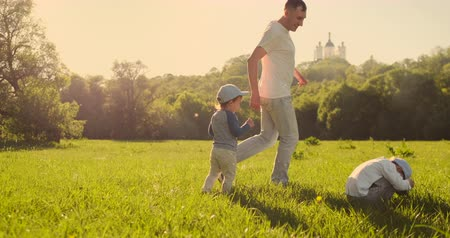 čelo : Father with two sons playing football in the meadow