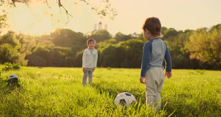 run down : Two cute little kids, playing football together, summertime. Children playing soccer outdoor.