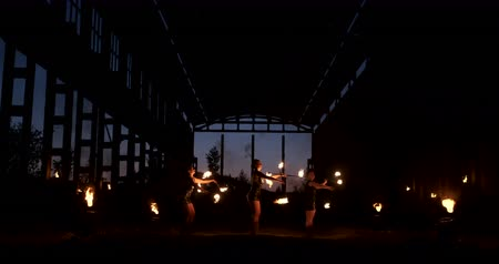 A group of people with fire and torches dancing at sunset in the hangar in slow motion. Fire show