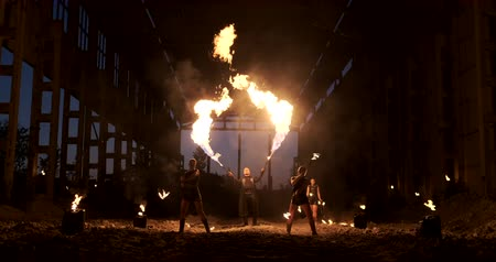 fire facilities : A group of professional artists with fire show the show juggling and dancing with fire in slow motion.