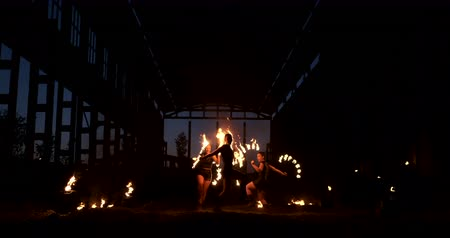gyúlékony : A group of people with fire and torches dancing at sunset in the hangar in slow motion. Fire show