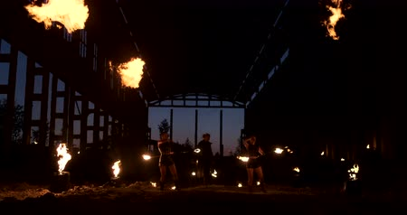 dvojitý : Four women in leather clothes with fire dance and show fire show a man with a flamethrower in the back plays with the flame in slow motion.