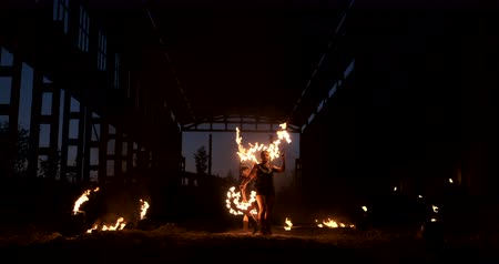 опасность : A group of professional artists with fire show the show juggling and dancing with fire in slow motion.