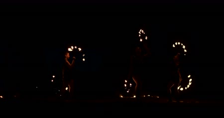 Slow motion: Professional fire performance three women with torches and a man with flamethrowers
