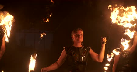 gyúlékony : Three women with burning hoops dance with fiery torches in leather clothes in a dark hangar demonstrating a circus fire show in slow motion.