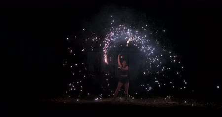 pirotecnia : A woman rotates a firework with flying sparks showing a thrilling pyrotechnic show in slow motion. Outdoor fire show Vídeos