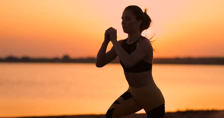 Side view of young woman doing squats outdoors. Side view of young fitness woman doing squats on standing by the lake on the sand at sunset the Slow motion.
