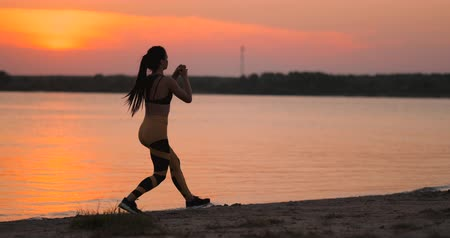 pista de corrida : A woman performs sit-UPS at sunset on the beach in slow motion. Exercise the muscles of the hips. Vídeos