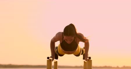 Beautiful woman athlete at sunset performs pushups on a parallel horizontal bar