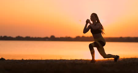 Fitness woman stretching doing lunge stretch exercise. Female athlete training lunges stretches outside in beautiful nature in Silhouette during beach sunset.