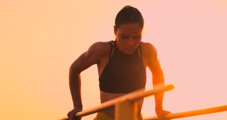 párhuzamos : A beautiful woman at dawn performs push-UPS on parallel bars in slow motion