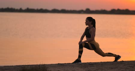 trabalhar fora : Woman is making lunges and crouching outdoors, training her body. Young slim woman is working muscles of her legs, hips and buttocks Vídeos