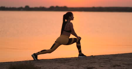 csikk : Woman is making lunges and crouching outdoors, training her body. Young slim woman is working muscles of her legs, hips and buttocks Stock mozgókép