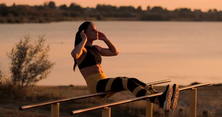 Abdominal muscles exercises. A young beauty athletic at sunset against the lake in summer woman in sportswear doing exercises for abs in slow motion on the bar.
