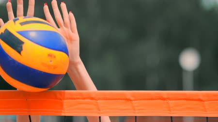 přestupek : SLOW MOTION, CLOSE UP, LOW ANGLE: Unrecognizable young female hands playing volleyball at the net. Offensive player spikes the ball and the opponent blocks it right above the net during a tournament.
