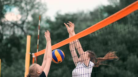 volleyball players : Young woman playing volleyball on the beach in a team carrying out an attack hitting the ball. Girl in slow motion hits the ball and carry out an attack through the net