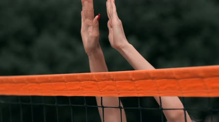 voleybol : SLOW MOTION, CLOSE UP, LOW ANGLE: Unrecognizable young female hands playing volleyball at the net. Offensive player spikes the ball and the opponent blocks it right above the net during a tournament.