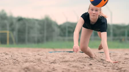 volleyball : Young female athlete dives into the sand and saves a point during beach volleyball match. Cheerful Caucasian girl jumps and crashes into the white sand during a beach volley tournament