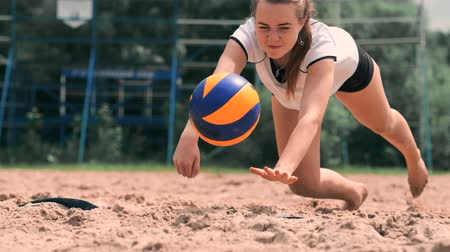 voleybol : Female volleyball player in the fall hits the ball in slow motion on the beach.