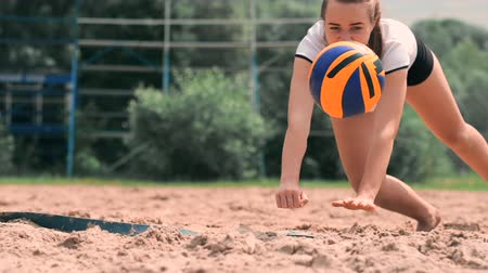 voleybol : Young female athlete dives into the sand and saves a point during beach volleyball match. Cheerful Caucasian girl jumps and crashes into the white sand during a beach volley tournament