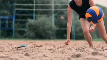 バレーボール : Female volleyball player in the fall hits the ball in slow motion on the beach.