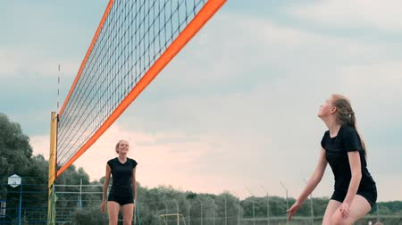 volleyball players : Women Competing in a Professional Beach Volleyball Tournament. A defender attempts to stop a shot during the 2 women international professional beach volleyball Stock Footage