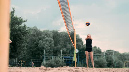 バレーボール : Women Competing in a Professional Beach Volleyball Tournament. A defender attempts to stop a shot during the 2 women international professional beach volleyball 動画素材
