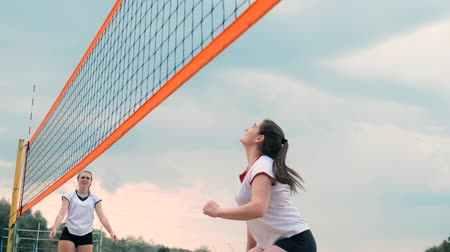receber : Women Competing in a Professional Beach Volleyball Tournament. A defender attempts to stop a shot during the 2 women international professional beach volleyball Stock Footage