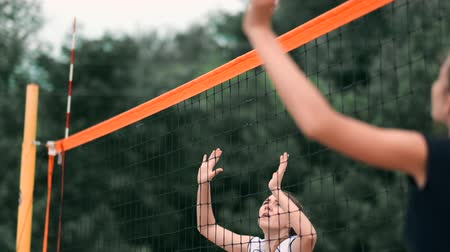 szórakoztatás : Women Competing in a Professional Beach Volleyball Tournament. A defender attempts to stop a shot during the 2 women international professional beach volleyball Stock mozgókép
