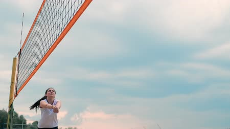 volleyball players : summer vacation, sport and people concept - young woman with ball playing volleyball on beach.