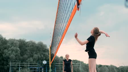 служить : Young woman playing volleyball on the beach in a team carrying out an attack hitting the ball. Girl in slow motion hits the ball and carry out an attack through the net