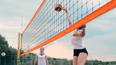 voleybol : Young woman playing volleyball on the beach in a team carrying out an attack hitting the ball. Girl in slow motion hits the ball and carry out an attack through the net