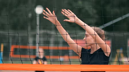 залп : Professional volleyball serve woman on the beach tournament. Volleyball net the player blocks the view when applying Стоковые видеозаписи