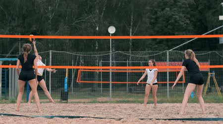 служить : Four girls volleyball players play on the beach in the summer participating in the tournament in slow motion on the sand.