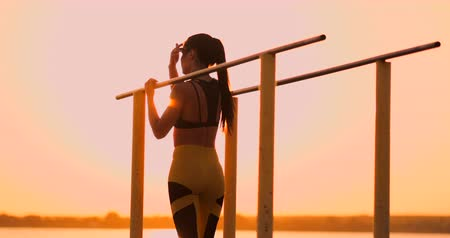 contra : Woman resting while standing in the sunset bar near the rear view. A beautiful brunette woman with long hair stands near horizontal horizontal bars resting in the sun. Stock Footage