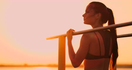 horizontal bar : Woman resting while standing in the sunset bar near the rear view. A beautiful brunette woman with long hair stands near horizontal horizontal bars resting in the sun. Stock Footage