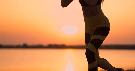 uyluk : Fitness woman stretching doing lunge stretch exercise. Female athlete training lunges stretches outside in beautiful nature in Silhouette during beach sunset.