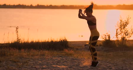bil : Fitness woman stretching doing lunge stretch exercise. Female athlete training lunges stretches outside in beautiful nature in Silhouette during beach sunset.