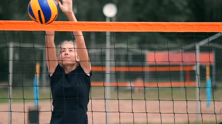 opponent : SLOW MOTION, CLOSE UP, LOW ANGLE: Unrecognizable young female hands playing volleyball at the net. Offensive player spikes the ball and the opponent blocks it right above the net during a tournament.