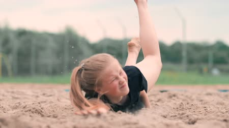 проходить : Slow motion: a Young woman jumping in the fall hits the ball on the sand. Volleyball player makes a team and plays the ball off in the fall