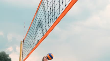 voleybol : Women Competing in a Professional Beach Volleyball Tournament. A defender attempts to stop a shot during the 2 women international professional beach volleyball Stok Video
