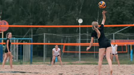 служить : Woman volleyball serve. Woman getting ready to to serve the volleyball while standing on the beach slow motion.