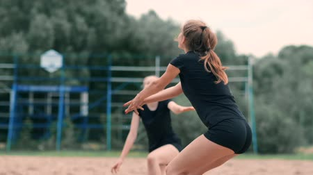 beach volleyball : Young woman playing volleyball on the beach in a team carrying out an attack hitting the ball. Girl in slow motion hits the ball and carry out an attack through the net