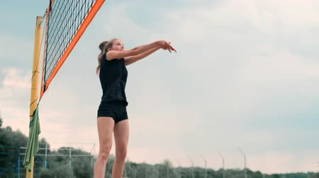 esportivo : Women Competing in a Professional Beach Volleyball Tournament. A defender attempts to stop a shot during the 2 women international professional beach volleyball Stock Footage