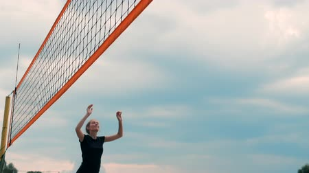 volleyball : Young woman playing volleyball on the beach in a team carrying out an attack hitting the ball. Girl in slow motion hits the ball and carry out an attack through the net