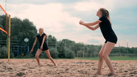 volleyball : Women Competing in a Professional Beach Volleyball Tournament. A defender attempts to stop a shot during the 2 women international professional beach volleyball Stock Footage