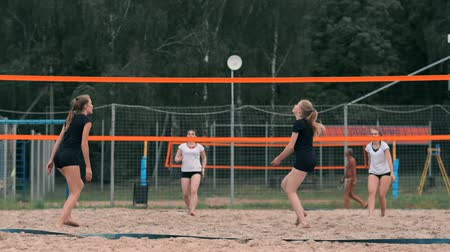 выполнять : Young woman playing volleyball on the beach in a team carrying out an attack hitting the ball. Girl in slow motion hits the ball and carry out an attack through the net