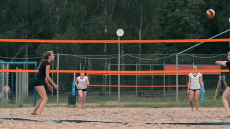хит : Young woman playing volleyball on the beach in a team carrying out an attack hitting the ball. Girl in slow motion hits the ball and carry out an attack through the net